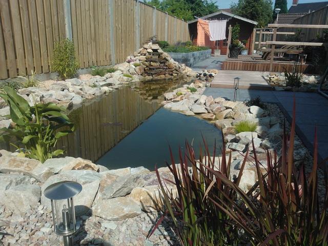Aanleg achter met natuursteen, vijver, en aanplanten borders (5)
